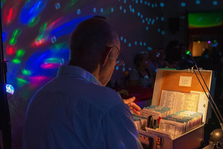 Der DJ sucht die nächste CD für die Tänzer