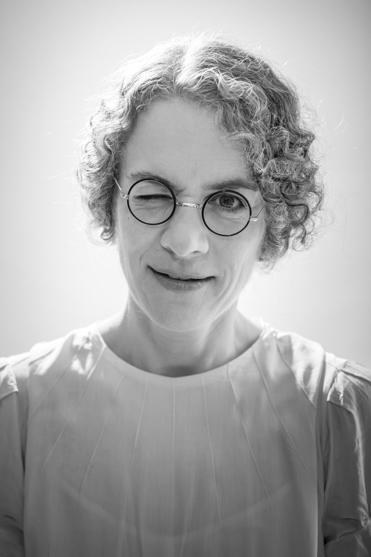 Die junge Frau im Stil der 20er Jahre zwinkert für das Vintage Portrait in die Kamera